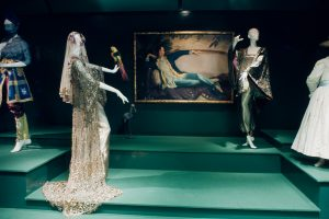 Mannequins in a dimly-lit room, dressed in feminine garments, with a painting of a woman lounging on the back wall
