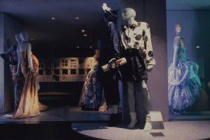 Mannequins dressed in feminine garments in a dimly-lit room
