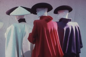 Exhibition display of three dressed mannequins with hats
