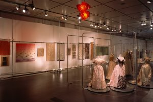 Exhibition display of 19th century feminine gowns and cloth paintings and prints