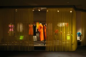 Exhibition display of mannequins behind gauze curtains