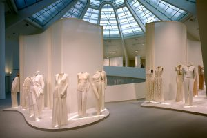 Exhibition display of mannequins in pale clothes and tall backdrops