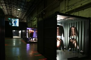 Dimply-lit exhibition display with garments suspended in shipping containers