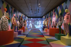 Long room exhibiting garments in feminine dress with brightly-coloured diamond-patterned walls and floor