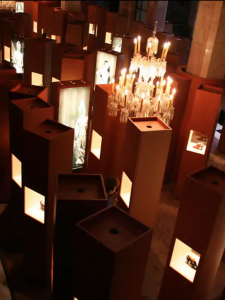 Exhibition display of plinths from above, interspersed with screens and some with shoes visible
