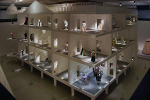 Exhibition display of an oversized doll's house with dressed mannequins