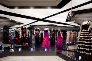 Exhibition display of dressed mannequins with mirrored background
