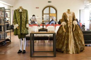 Exhibition display of dressed mannequins in period costume beside scientific apparatus with arched window in background