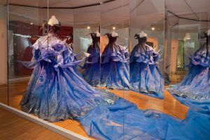 Exhibition display of dressed mannequins in blue dress with a train reflected in mirror in background