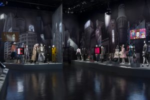 Exhibition display of dressed mannequins with an urban backdrop