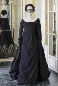 mannequin in dark long dress and masked eyewear