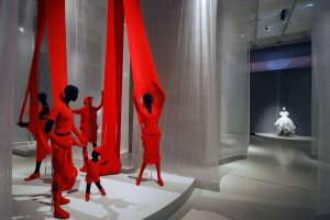 Exhibition display of mannequins dressed in red reaching up to red drapes
