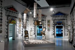 Exhibition display of chair suspended in air against backdrop of printed textiles