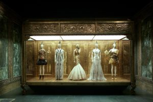 Exhibition display of five dressed mannequins within elaborate gold setting
