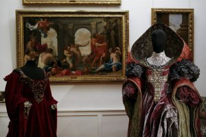 Exhibition display of dressed mannequins in 17th Century garments with hoods in front of portrait