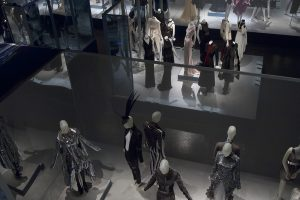 Exhibition display of mannequins in grey, dimly-lit setting