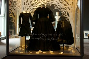Exhibition display of three mannequins in black garments