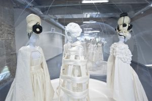 Exhibition display of mannequins dressed in white in perspex bubbles