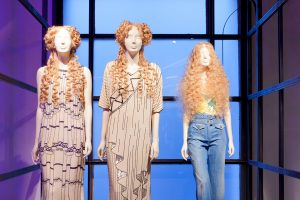 Exhibition display of three dressed mannequins with curly wigs