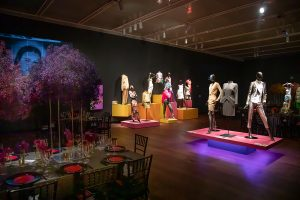 Exhibition display of dressed mannequins on coloured plinths with table and chairs laid for dinner in foreground
