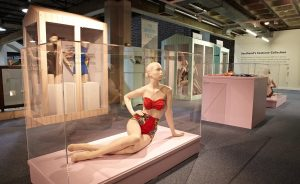 Exhibition display of dressed mannequins with one sitting in foreground in swimwear