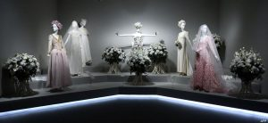 Exhibition display of dressed mannequins in bridal style veils and ghostly light