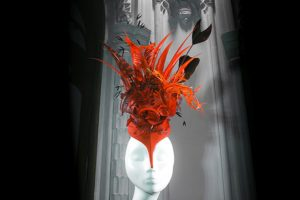 Exhibition display of red headdress on mannequin head