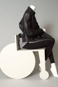 Exhibition display of mannequin in white stylised wheelchair