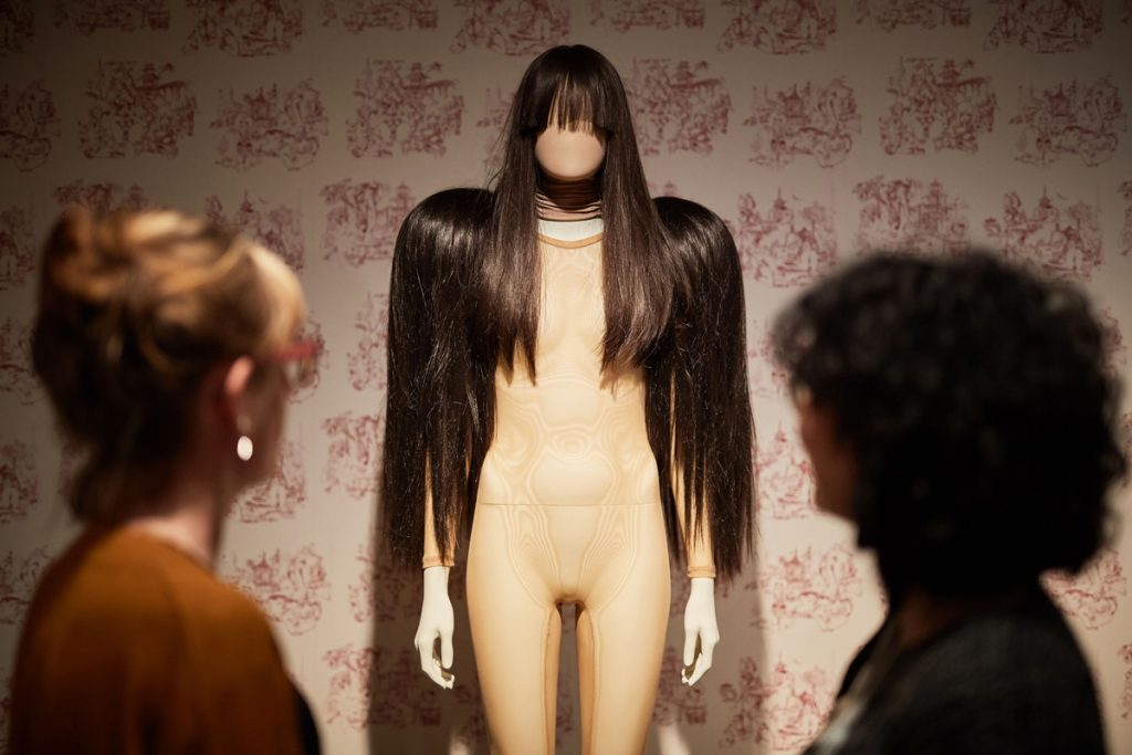 A mannequin with long brown hair and fringe, in front of a wall-papered wall, wearing a sheer body stocking with wigs of long brown hair on each shoulder