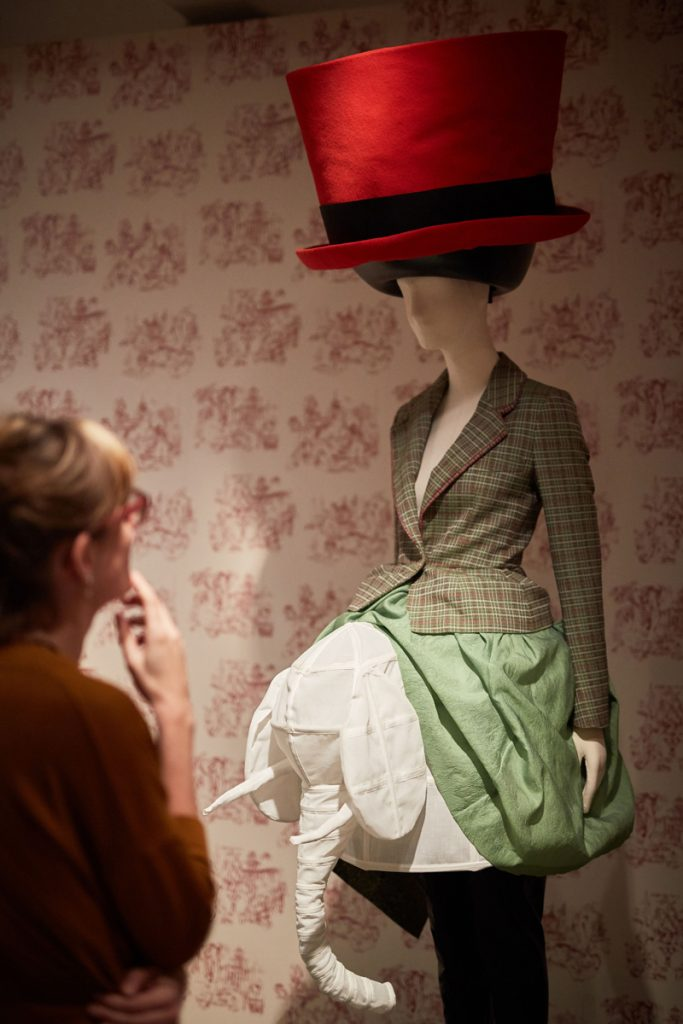 A mannequin in front of a wall-papered wall, wearing an oversized red brimmed hat, a tailored and fitted green/brown jacket, and a green and white skirt featuring a cloth elephant head in the front