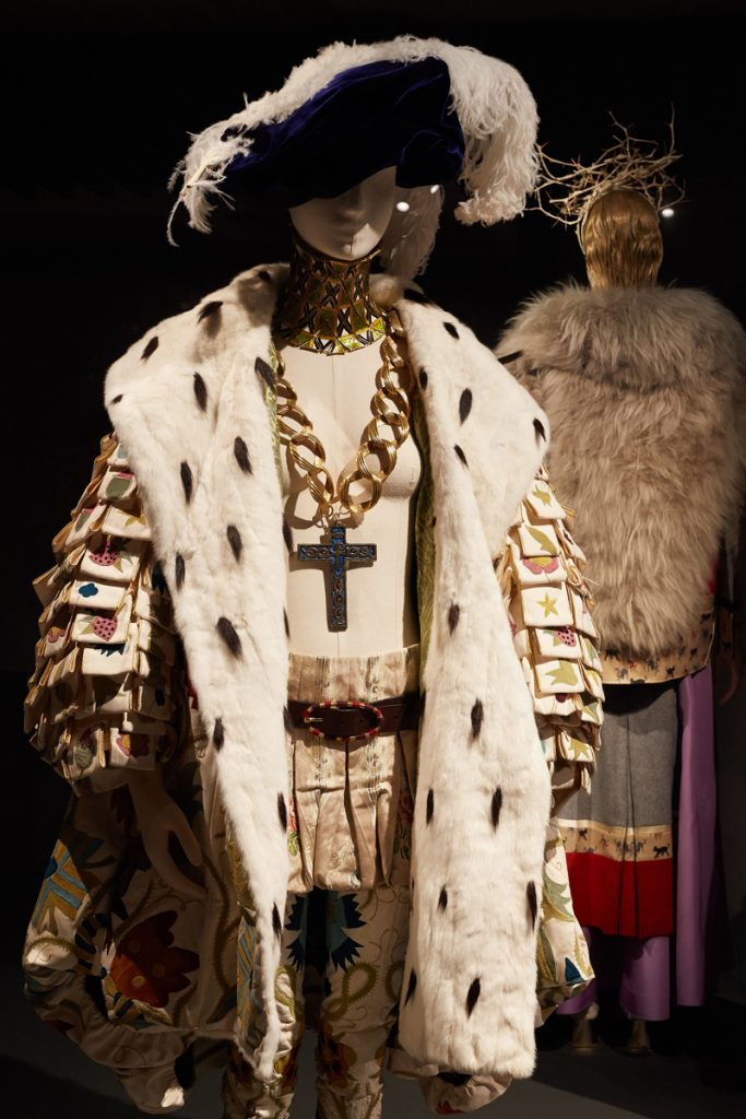 A mannequin dressed in a Tudor-style overcoat, an oversized necklace with a cross, and a white-feathered black hat