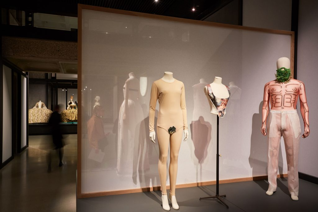 A display of two female and one male mannequins, dressed in pale garments emphasising the attributes of the physical body