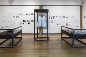 Exhibition display of glass cases containing garments
