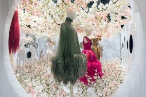 Exhibition display of dressed mannequins in spray of flowers
