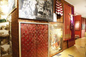 Exhibition display of garments alongside paintings