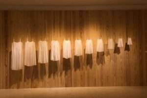 Exhibition display of white dresses hanging
