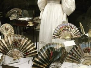 Exhibition display of fans in foreground of dressed mannequin