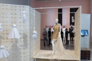 Exhibition display of dressed mannequins with small wedding dresses suspended to the side
