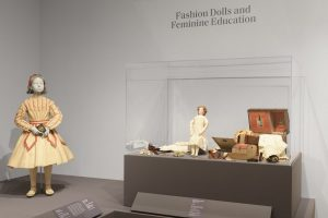 Exhibition display of dressed mannequin of a child and of dolls