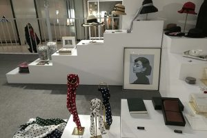 Exhibition display of accessories and hats on plinths with photo of audrey hepburn