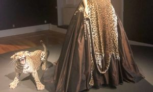 Exhibition display of dressed leopard beside mannequin