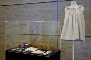 Exhibition display of dressed mannequin torso in smock beside a glass case of objects