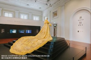 Exhibition display of mannequin in gold ensemble on a plinth