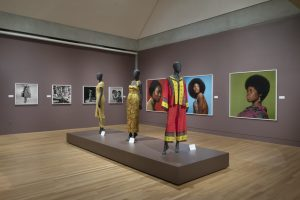 Exhibition display of dressed mannequins with portraits in background