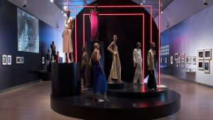 Exhibition display of dressed mannequins on a raised plinth with neon lighting