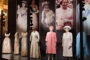 Exhibition display of dressed mannequins with Queen Elizabeth II garments against a backdrop