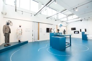 Exhibition display of dressed mannequins and plinths on blue floor
