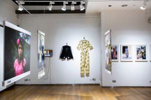 Exhibition display of garments suspended on wall, and hanging images