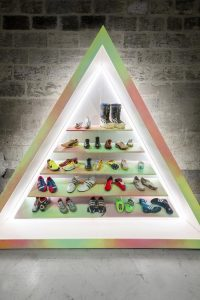 Exhibition display of trainers in a triangle-shaped plinth