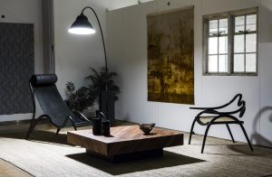 Exhibition display of chairs and coffee table underneath a large anglepoise lamp